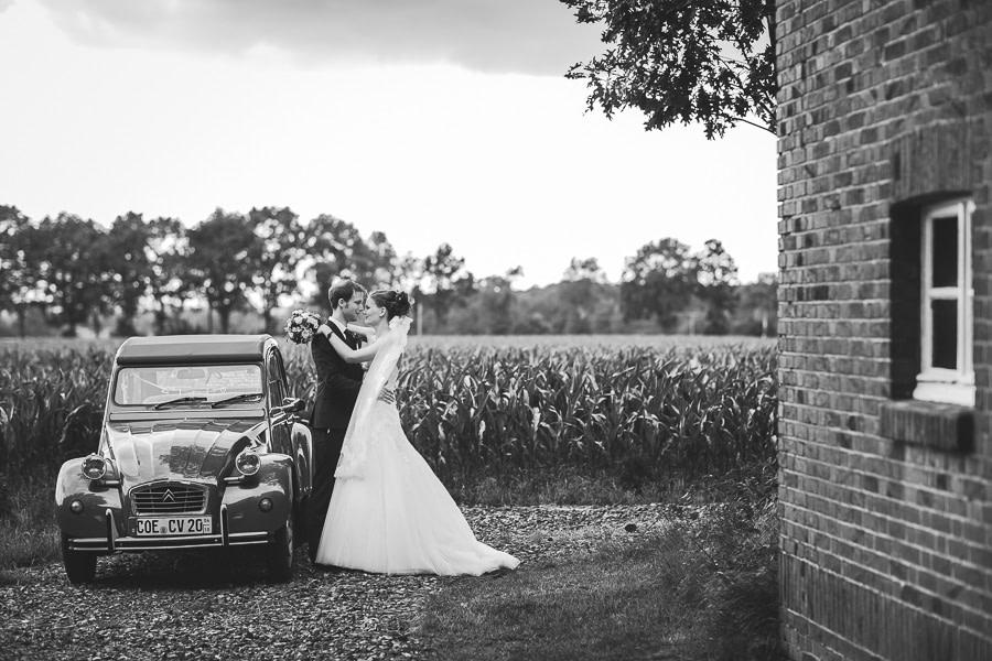 Eine sogenannte Ente als Oldtimer Hochzeitsauto daneben das Brautpaar am knutschen