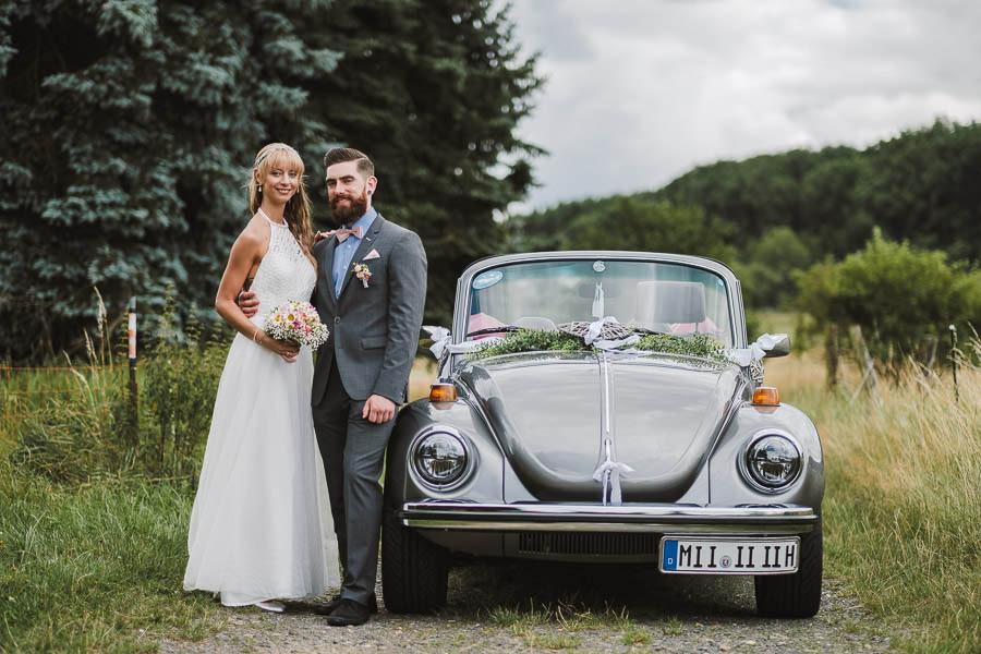 Brautpaar posiert am VW Käfer als Hochzeitsauto