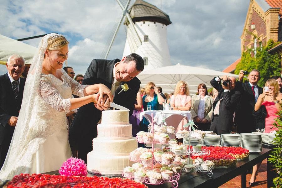 Hochzeitspaar schneidet 3-stöckige Torte draußen und im Hintergrund die Elfrather Mühle