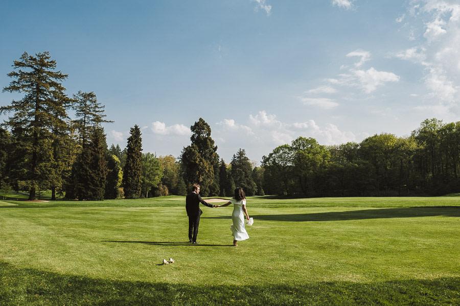 Brautpaar spaziert lässig auf Golfplatz von Schloss Kronberg