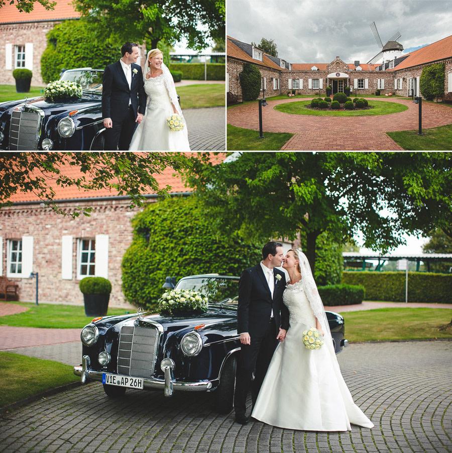 Brautpaar steht vor ihrer Hochzeitslocation Elfrather Mühle neben einem Oldtimer von Mercedes