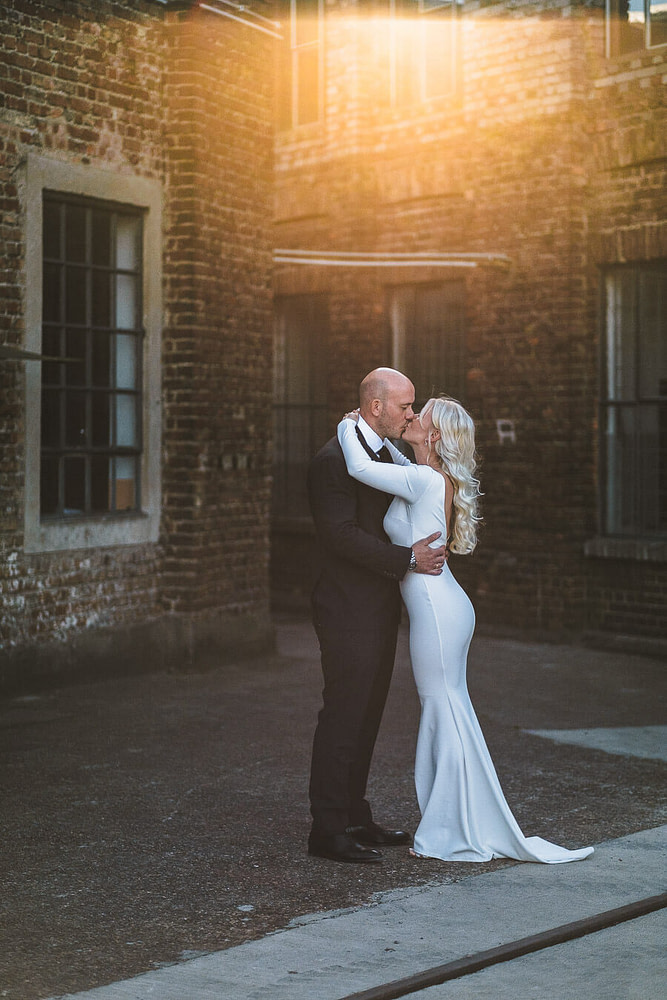 brautpaar steht vor backstein gebaeude alte fabrik hanau und kriegt sonnenlicht von hinten