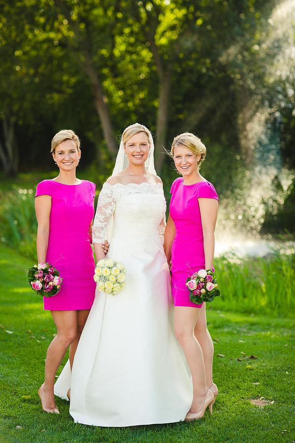 Foto der Braut mit ihren zwei Schwestern beide im gleichen Kleid draußen im Rahmen der Gruppenfotos für die Hochzeit