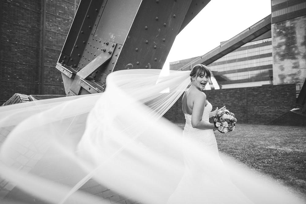 Witziges Hochzeitsfoto mit Braut auf Industriegelände. Schleier fliegt weg.