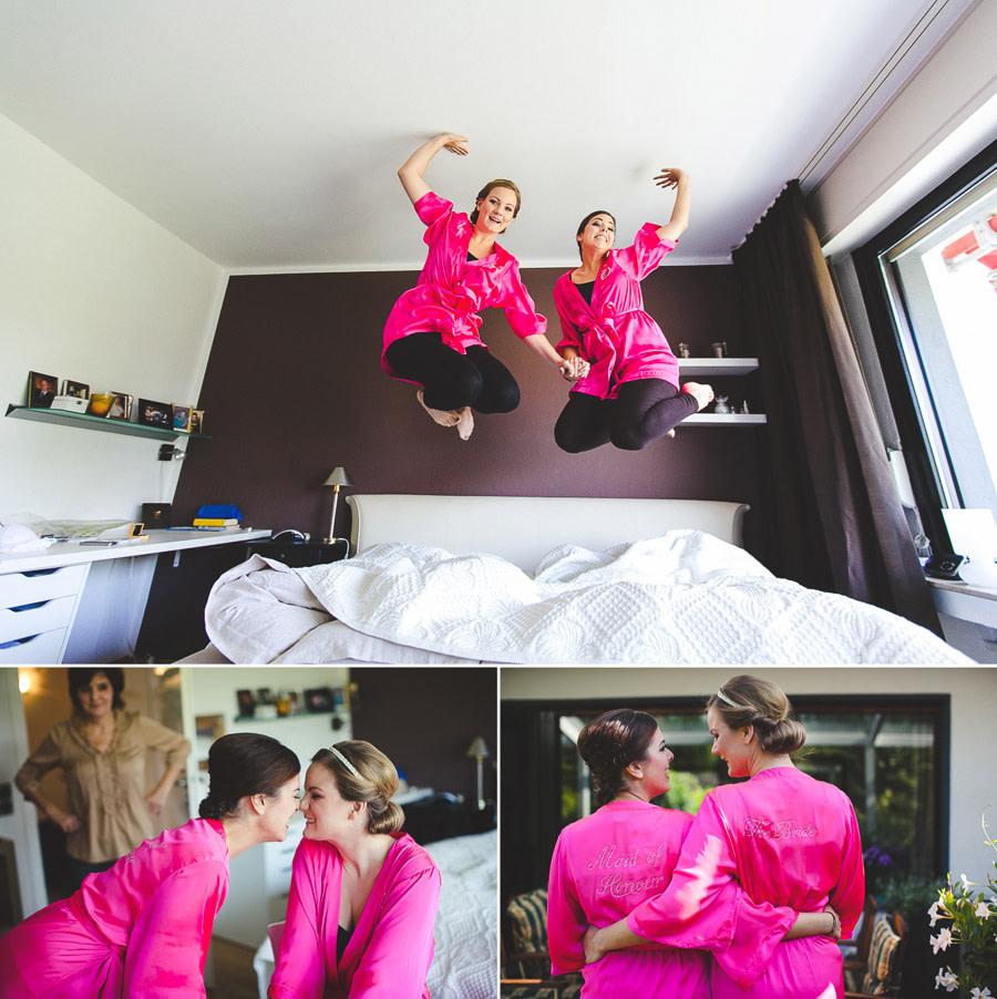 Braut und Trauzeugin hüpfen mit pinken Hochzeitsroben lustig auf Bett