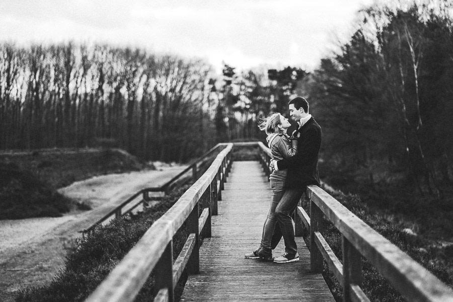 Paar umarmt sich beim windigen Wetter auf Brücke