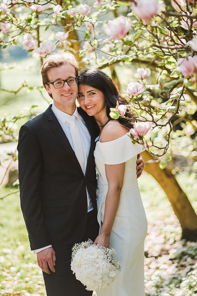 Brautpaar lächelt beim Fotoshooting vor Pfingstbaum