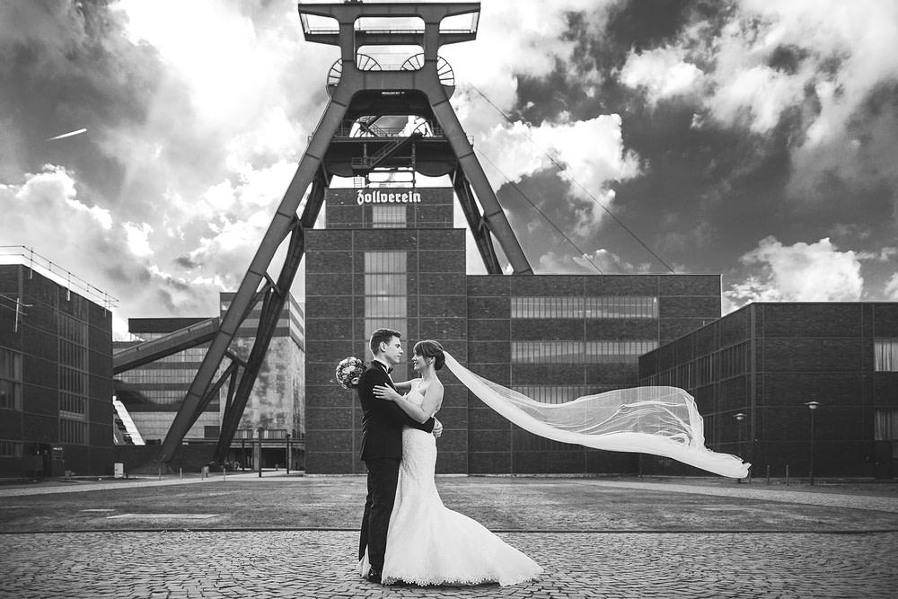 geiles Hochzeitsfoto auf der Zeche Zollverein in Essen. Schleier der Braut fliegt cool in der Luft.