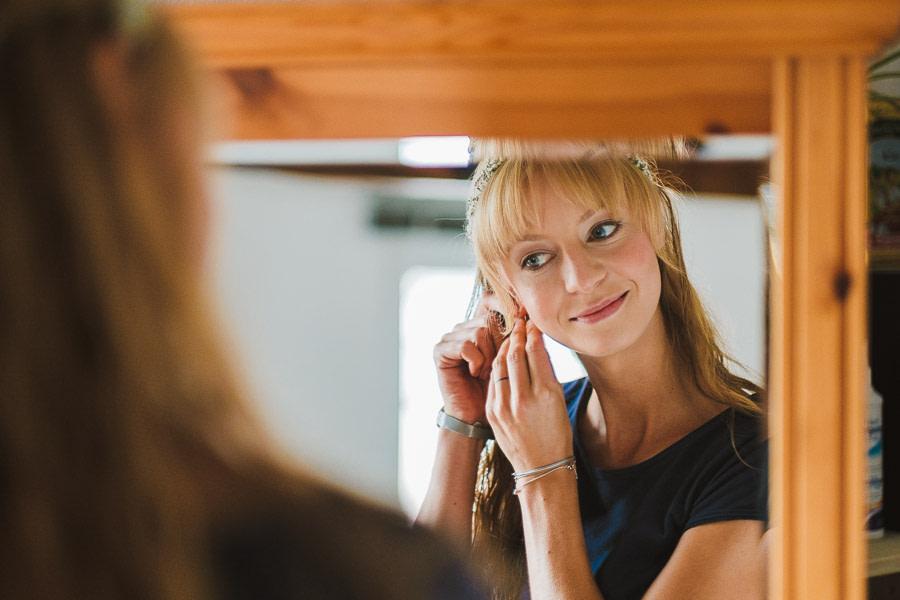 Glücklcihe braut schaut sich im Spiegel an und steckt ihre Ohringe