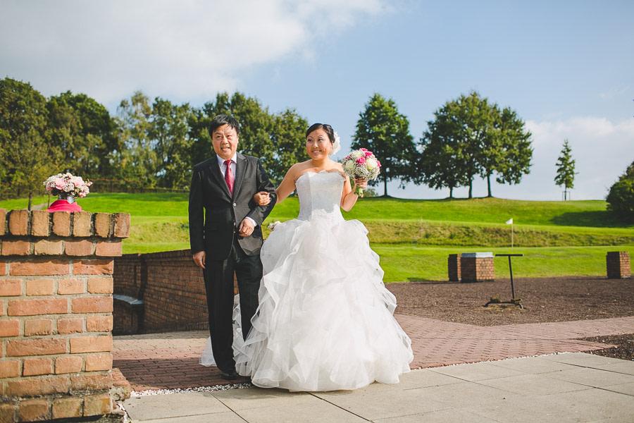 Braut asiatischer Abstammung mit großem Hochzeitskleid à la Prinzessin Sissi wartet mit Vater Chinese kurz vor dem Einzug freie Zeremonie bei Sonnenschein