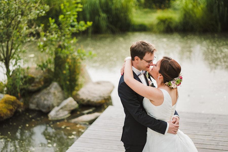 Hochzeitspaar umarmt sich am Wasser
