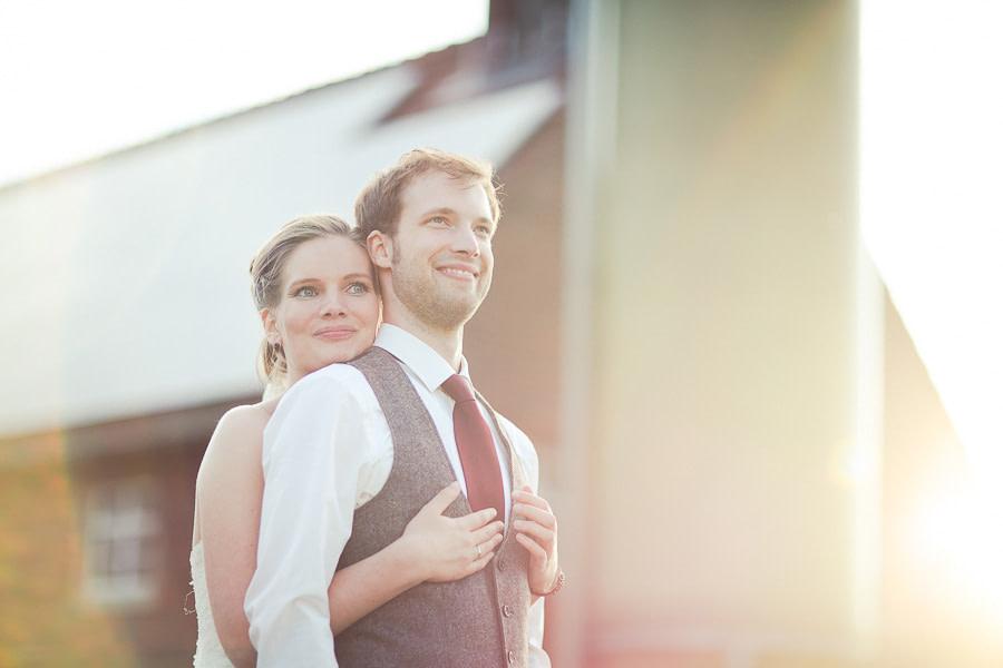 Braut umarmt Bräutigam von hinten beide lächeln, erstrahlt vom Licht mit tollen Lichteffekten durch Gegenlicht