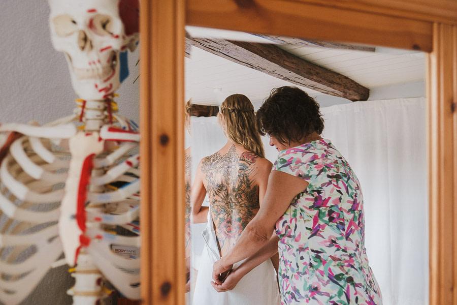 Braut mit Rückentattoo zieht ihr Kleid an