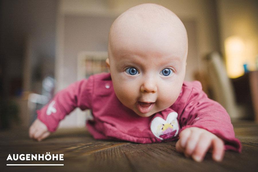 Baby auf krabbelt auf Holztisch fotografiert auf Augenhöhe