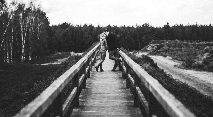 liebespaar küsst sich auf einer brücke