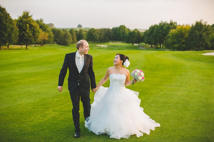 Chinesische Braut und deutscher Bräutigam als Brautpaar laufen glücklich aufm gepflegten Rasen von Golfclub Kosaido in Düsseldorf