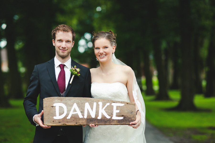 Brautpaar hält ein selbstgemachtes Holzschild mit Danke